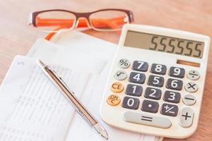 estação de trabalho com calculadora, caneta e óculos