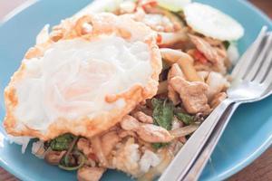 arroz frito de manjericão com porco e um ovo frito