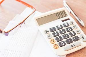 caderneta de conta bancária com caneta, calculadora e óculos