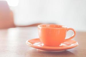 mini xícara de café laranja em uma mesa de madeira foto