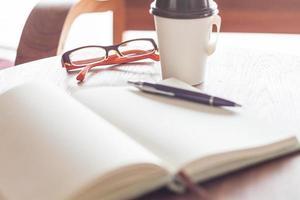 óculos com uma xícara de café em uma cafeteria foto
