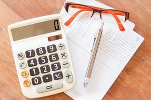 vista superior de uma calculadora, caneta, óculos e notas