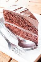 pedaço de bolo de chocolate servindo com garfo e colher