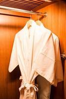 mantos brancos em cabides de madeira foto