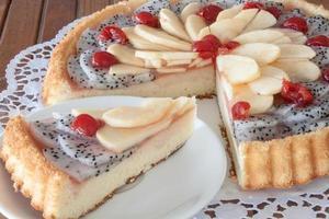 bolo coberto com fruta do dragão, maçãs e cerejas