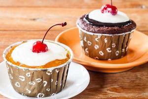 dois cupcakes em uma mesa de madeira foto