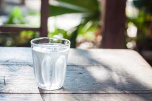 copo de água fria em uma mesa de madeira