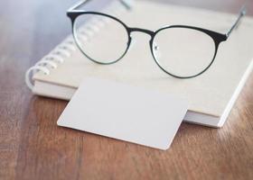 par de óculos com um cartão de visita em branco