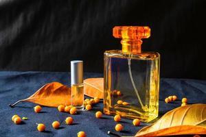 frasco de perfume de ouro e folhas de laranja foto