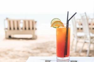 copo de coquetel de frutas com vista para o mar