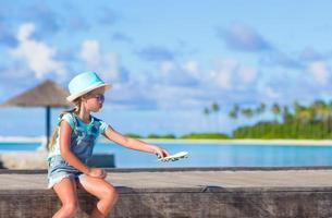 menina brincando com um avião de brinquedo