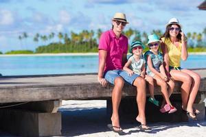 família sentada na praia foto
