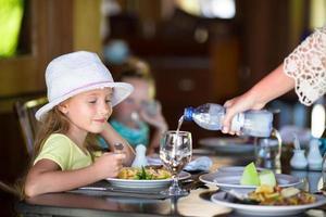 garota jantando em restaurante ao ar livre foto