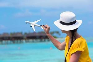 mulher brincando com um avião de brinquedo na praia