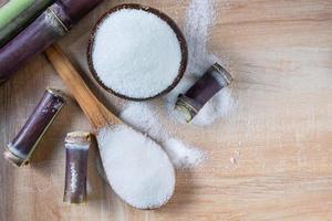 açúcar branco em uma tigela de madeira sobre a mesa foto