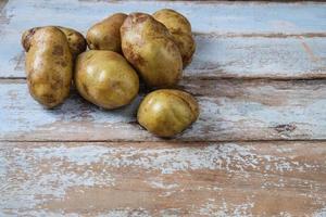 batatas em um fundo de madeira foto