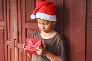 menino com caixa de presente no dia de natal foto