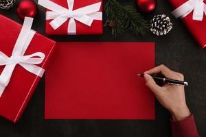 mãos escrevendo maquete de cartão vermelho