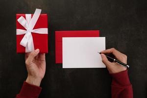 mãos escrevendo maquete de cartão branco