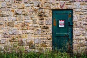 porta de metal verde na parede de pedra