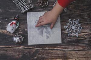 caixa de presente de Natal em uma mesa de madeira e mão consertando o arco foto