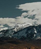 montanha coberta de neve sob nuvens brancas durante o dia foto