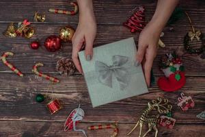 mãos com caixa de presente de Natal em um fundo de madeira foto