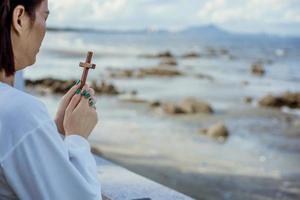 mulher asiática rezando com uma cruz de madeira na praia foto