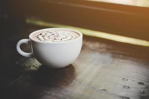 uma xícara de café na mesa de madeira foto