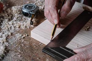 carpinteiro fazendo medições em uma mesa foto