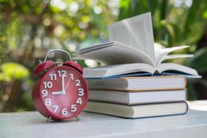 despertador vermelho com livro sobre fundo de jardim natural foto
