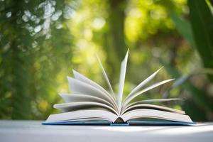 close-up de livro aberto com fundo natureza bokeh