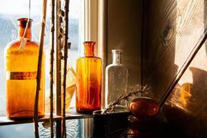 garrafas de vidro em uma prateleira perto de uma janela