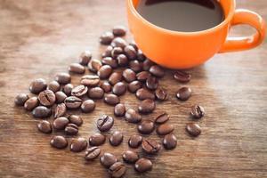 grãos de café com uma xícara de café em uma mesa de madeira