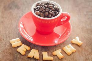 grãos de café em uma caneca com letras do alfabeto