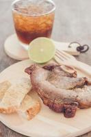 bife de porco em um prato de madeira