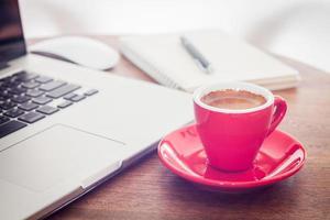 xícara de café vermelha em uma mesa com um laptop foto
