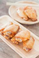 asas de frango grelhadas em um prato de madeira
