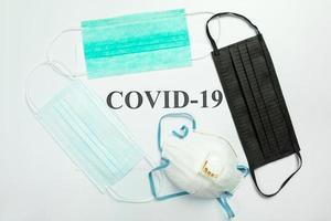 máscaras de proteção médica na mesa com covid-19 palavra
