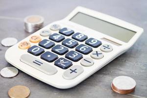 calculadora e moedas em um fundo cinza foto