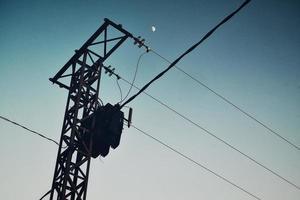 lua e linhas de energia elétrica no céu foto