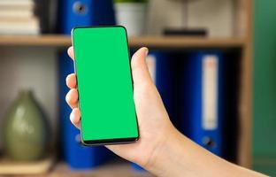 mulher segurando uma tela verde do smartphone foto