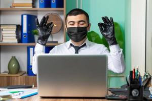 jovem empresário trabalhando em um laptop com máscara protetora médica preta e luvas