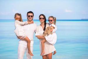 família em roupas brancas em uma praia foto