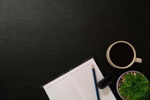 mesa preta com café e ferramentas de escritório
