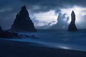 silhuetas de rochas no mar à noite