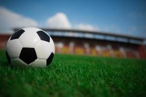 uma bola de futebol na grama com o fundo do estádio foto