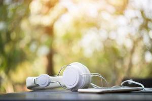 fones de ouvido brancos na mesa de madeira com fundo natural
