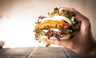 mãos segurando hambúrguer sobre a tábua