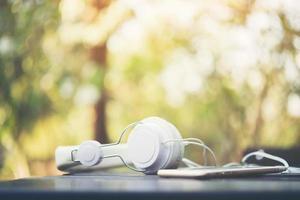 fones de ouvido brancos na mesa de madeira com fundo natural foto